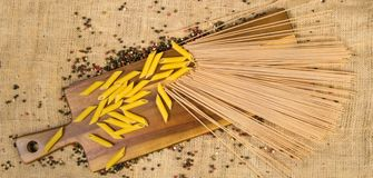 Italian spaghetti and pasta with decorative pepper on a wooden board and canvas Royalty Free Stock Photo