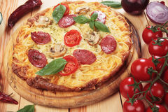 Italian spaghetti pizza. With pepperoni, mushrooms and tomato Stock Photography