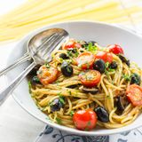 Italian spaghetti puttanesca pasta. Close up of homemade Italian spaghetti puttanesca pasta stock photo