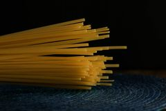 Italian spaghetti raw pasta, dark background black and deep blue stock photo