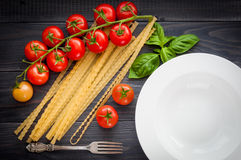 Italian spaghetti, served plate, on a wooden table with bunch tomatoes. Top view Stock Photos