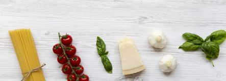 Italian spaghetti, tomatoes, parmesan, basil and garlic, overhead view. Igredients for cooking pasta. Copy space stock photography