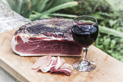 Italian speck and red wine. A glass of italian red wine is on a wooden tray, near some slices and one entire piece of speck not sliced yet Royalty Free Stock Images