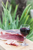 Italian speck and red wine. A glass of italian red wine is on a wooden tray, near some slices and one entire piece of speck not sliced yet. The green plants of a stock photos