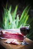 Italian speck and red wine. A glass of italian red wine is on a wooden tray, near some slices and one entire piece of speck not sliced yet. The green plants of a royalty free stock photography