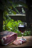 Italian speck and red wine. A glass of italian red wine is on a wooden tray, near some slices and one entire piece of speck not sliced yet. The green plants of a stock photography