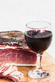 Italian speck and red wine. A glass of italian red wine is on a wooden tray, near some slices and one entire piece of speck not sliced yet.nThe scene is all royalty free stock photos