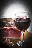 Italian speck and red wine. A glass of italian red wine is on a wooden tray, near some slices and one entire piece of speck not sliced yet.nThe scene is all stock photo