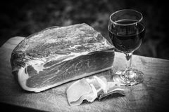 Italian speck and red wine. A glass of italian red wine is on a wooden tray, near some slices and one entire piece of speck not sliced yet.nThe scene is all Royalty Free Stock Images