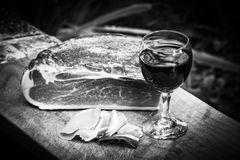 Italian speck and red wine. A glass of italian red wine is on a wooden tray, near some slices and one entire piece of speck not sliced yet.nThe scene is all Stock Image