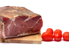 Italian speck on wooden chopping board and tomatoes Stock Photo