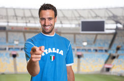 Italian sports fan pointing at camera at soccer stadium Stock Image