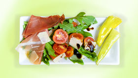 Italian starter. Square white plate with various delicious food as Italian starter Royalty Free Stock Photography