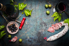 Italian still life with salami, red wine, olives and grape leaves on dark rustic background, top view Royalty Free Stock Images