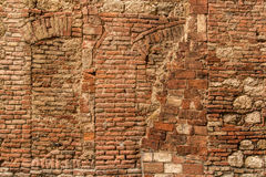 Italian stone wall. Texture of typical Italian old stone and brick wall. Traces of the pledged old windows Royalty Free Stock Photos