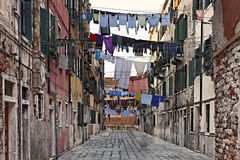 Italian street. Traditional Italian street with clothes hanging out to dry between old houses, somewhere in Venice royalty free stock images