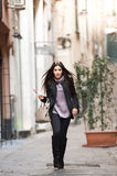 Italian streets. A young beautiful dark hair woman with a handbag and boats walking with intent in the beautiful narrow streets of Genoa, an old Italian harbor royalty free stock images