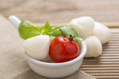 Italian style mozzarella, salad and basil on wooden background Royalty Free Stock Image