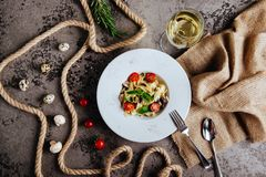 Italian style pasta dinner. Spaghetti with tomato and basil in plate on wooden board stock image