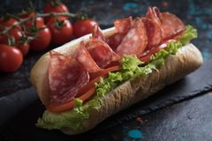 Italian submarine sandwich. With cured meat, lettuce and tomato Stock Photo