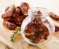 Italian sun dried tomatoes in a glass jar on a wooden board. Royalty Free Stock Images
