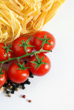 Italian tagliatelle background. Close up of italian pasta and tomatoes over white Stock Photos