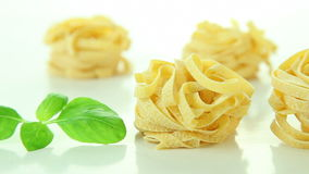 Italian tagliatelle pasta and basil on white background stock footage