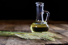 Italian tasty food, olive oil and cereal ears. Wooden table stock photos