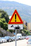 Italian temporary warning sign `Other danger` with additional panel `Construction vehicles at work`. On the road stock photography