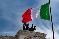 Italian flag of Italy green white and red in rome. Italian three colors flag of Italy on the blue sky background stock image