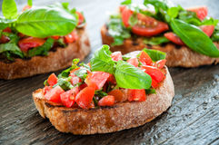 Italian tomato bruschetta with chopped vegetables. Herbs and oil on grilled or toasted crusty ciabatta bread Royalty Free Stock Images