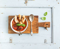 Italian tomato, garlic and basil soup Pappa al Pomodoro in metal bowl with bread on rustic wooden board over light blue Royalty Free Stock Image