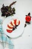 Italian tomato and mozzarella Caprese salad seasoned with pepper Stock Image