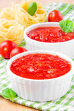 Italian tomato sauce in a white cup with raw pasta, basil and ch Royalty Free Stock Photography