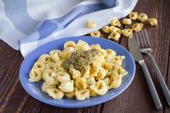 Italian Tortellini with pesto sauce. Italian Tortellini on a blue plate with pesto sauce Stock Photography