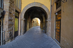 Italian town. Atmospheric passage with stone slab floor and arched tunnel in a medieval town in Italy Stock Photography