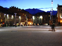 Italian town square. People walking through Aosta's town square at night , with the Italian Alpes in the background Stock Photos