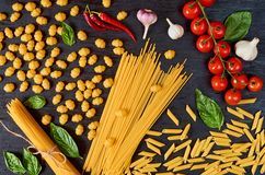 Italian traditional food, spices and ingredients for cooking as basil, cherry tomatoes, chili pepper, garlic and various pasta stock image