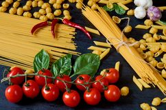 Italian traditional food, spices and ingredients for cooking as cherry tomatoes, chili pepper, garlic, basil leaves and pasta stock image