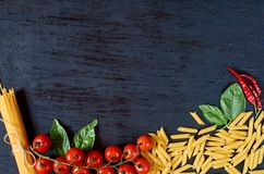 Italian traditional food, spices and ingredients for cooking: basil leaves, cherry tomatoes, chili pepper and various pasta stock photos