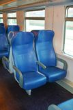 Italian train chairs, Venice, in the evening. Empty and blue chairs, beautiful windows, in a speedy Italian train, in Venice, Italy, Europe. Lights on, in the Stock Image