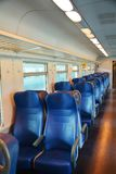 Italian train, inside, Venice, in the evening. Clean empty and blue chairs in a speedy Italian train, in Venice, Italy, Europe. Lights on, in the evening Stock Photo