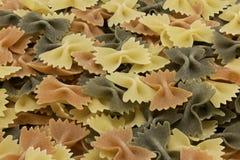 Italian tri-colored raw farfalle. Colorful Italian tri-colored raw farfalle as a background Stock Photo