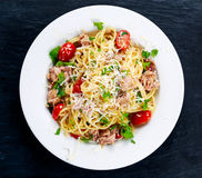 Italian Tuna Pasta spaghetti with tomato, chili, Parmesan cheese and wild rocket lives. on old blue stone background Royalty Free Stock Image