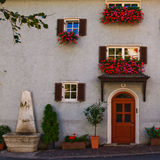 Italian Tyrol house. Outdoor image of a typical south tyrol house with colorful flowers and fountain royalty free stock photos
