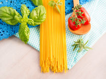 Italian uncooked spaghetti with tomatoes and basil Stock Photos