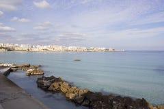 Italian vacation - Otranto in Puglia. Otranto: rocks and city on the horizon Stock Image