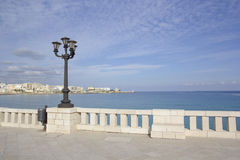 Italian vacation - Otranto in Salento, Puglia. Seafront. Otranto: waterfront with lamppost and city in the background Royalty Free Stock Photos