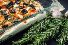 Italian vegetarian focaccia of homemade bread with olives, rosemary and garlic Stock Photos