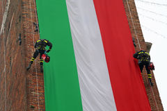 Italian very brave fearless firefighters climb the old tower wit. H a big Italian flag Stock Images